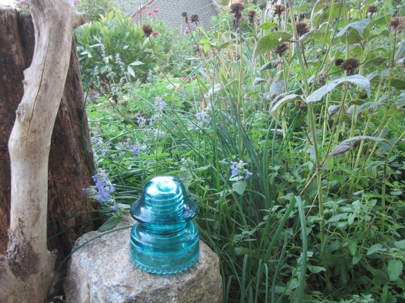 catmint growing around some garden art